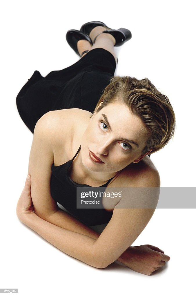 sexy young beautiful caucasian woman lounges gracefully while wearing a black evening gown with her hair slicked back and red lipstick : Foto de stock