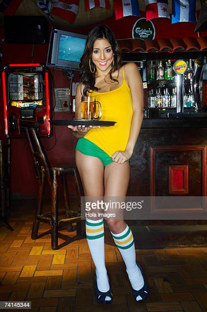 Sexy young waitress carrying tray with drinks