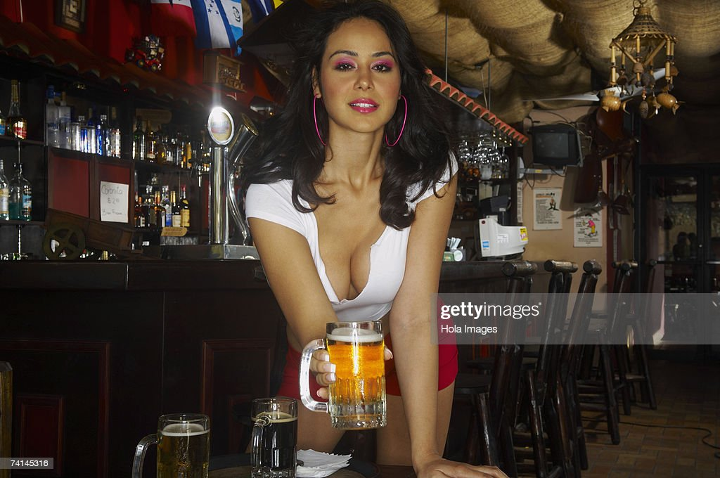 Sexy young waitress serving beer in bar