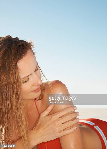 セクシーな若い女性は彼女の手で日焼け止め