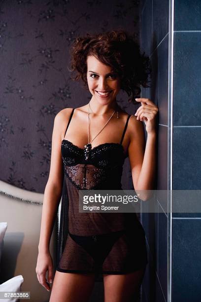 sexy young woman in bedroom smiling - women in slips stock photos and pictures
