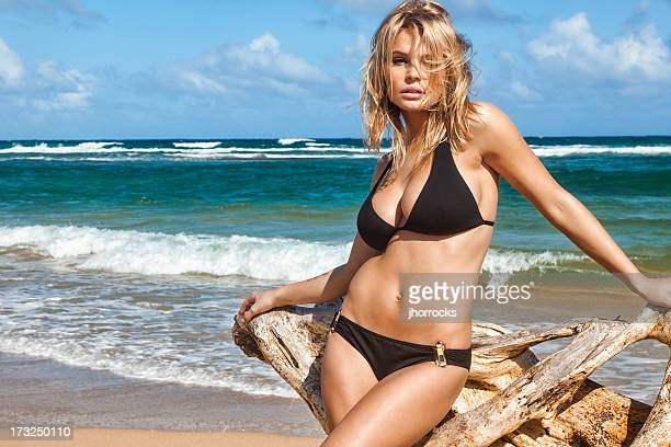 sexy young woman in black bikini posing with driftwood - skinny black woman stock photos and pictures