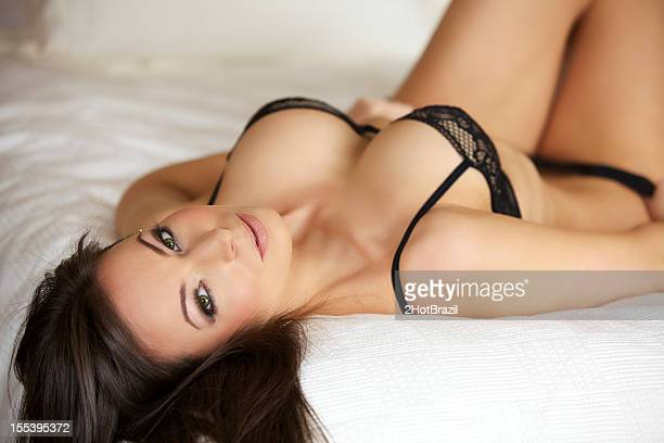 sexy young woman in lingerie on a bed - booby stock pictures, royalty-free photos & images