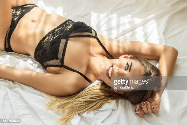 sexy young woman in lingerie posing on the bed - garter belt models stock pictures, royalty-free photos & images