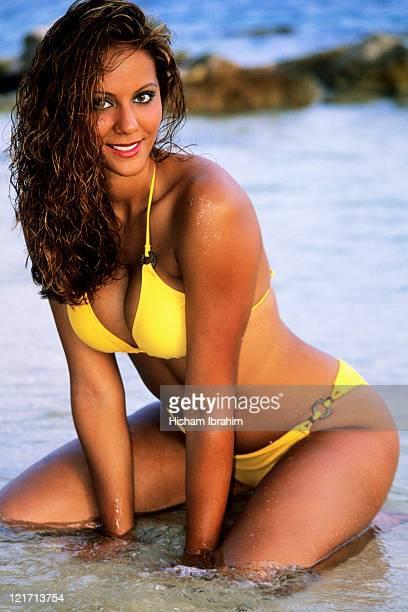 Sexy young woman in yellow bikini sitting on beach