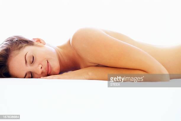 セクシーな若い女性に横における上半身裸のベッド