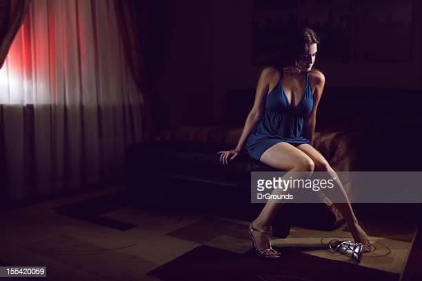 sexy giovane donna seduta da sola in camera da letto - bordello foto e immagini stock