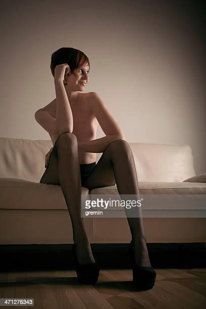 sexy junge frau sitzt auf der couch - junge frau strumpfhose stock-fotos und bilder