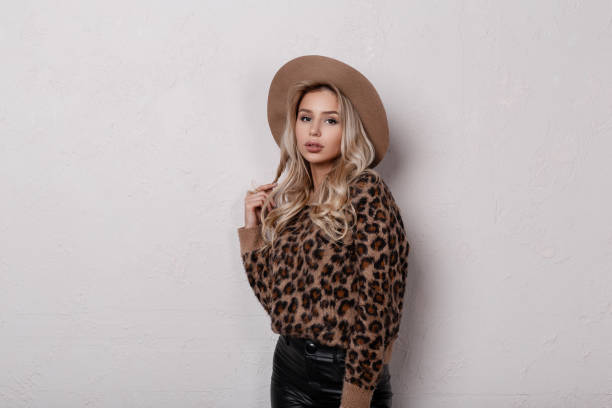 86f1820bad9c5 ... Sexy young woman with natural make-up in stylish leopard sweater in  fashionable black leather ...