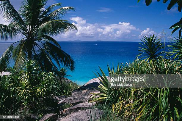Seychelles Fregate Island View through rocks and foliage toward the turquoise sea with islands of Praslin and La Digue on the horizon