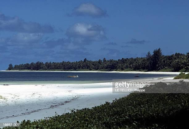 Seychelles Islands En 1972 aux îles Seychelles un bateau à moteur à l'ancre et un pêcheur en pirogue sur une plage bordée de végétation