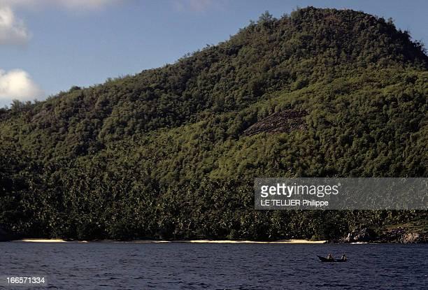 Seychelles Islands En 1972 aux îles Seychelles une pirogue sur la mer devant une montagne recouverte de végétation