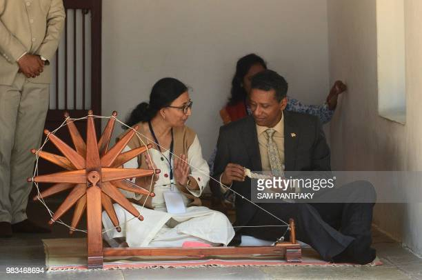 Seychelles President Danny Faure takes lessons on a spinning wheel during his visit to the Gandhi Ashram where Indian independence icon Mahatma...