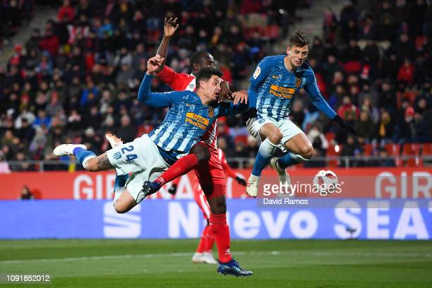 Seydou Doumbia of Girona FC competes for the ball with Jose Gimenez and Santiago Arias of Atletico de Madrid during the Copa del Rey Round of 16...
