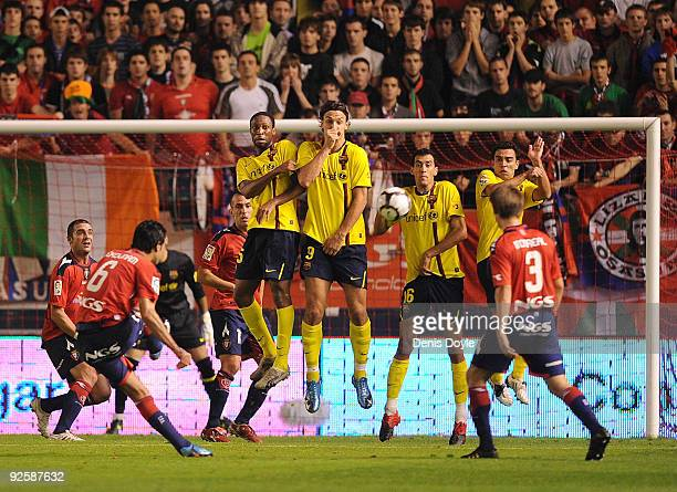 Seydou Keita Zlatan Ibrahimovic Sergio and Xavi Hernandez of Barcelona block a free kick by Javad Nekouman of Osasuna during the La Liga match...