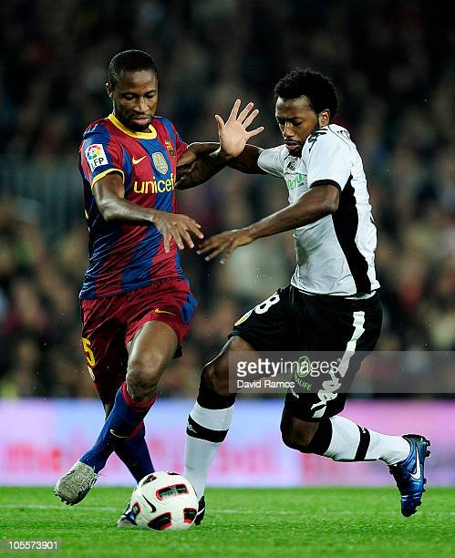Seydou Keyta of Barcelona duels for the ball with Manuel Fernandes of Valencia during the La Liga match between Barcelona and Valencia at the Camp...