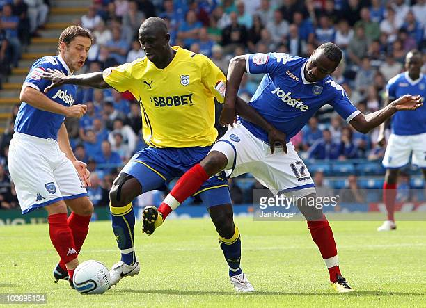 Seyi Olifinjana of Cardiff City holds off Michael Brown and John Utaka of Portsmouth during the npower Championship match between Portsmouth and...