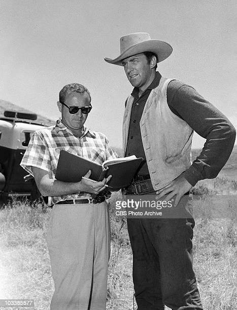 GUNSMOKE Seymouir Burns directing left and James Arness as Marshal Matt Dillon in 'Overland Express' Image dated June 5 1957
