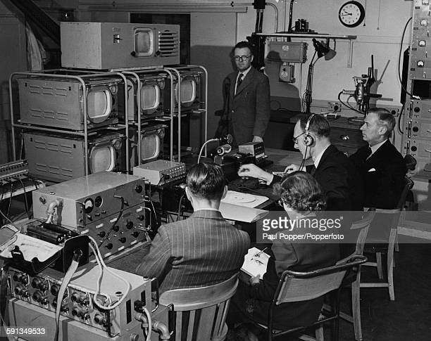 Seymour de Lotbiniere Head of Outside Broadcasts for BBC TV looks at a series of television screen as he controls arrangements for the televising of...