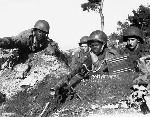Sfc. Major Cleveland, weapons squad leader, points out a Communist-led North Korean position to his machine gun crew. They are fighting with the 2nd...