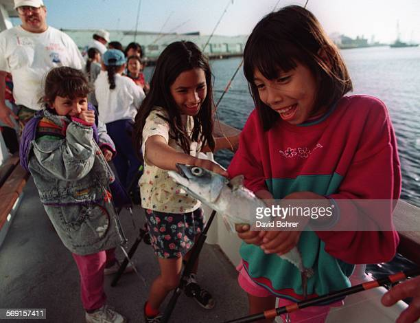 SFFish30326DB Sharing the joy and the gross–ness of their friend's catch Teresa Torres Daisy Trejo 8 watch as Consuelo Rodriguez 10 reluctanly holds...