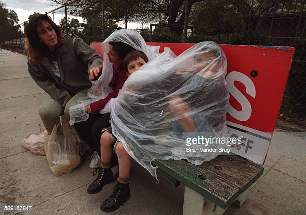 SFValHail9bv2–17/NORTHRIDGE –– A family who would not give their names wraps themselves in plastic against an impending downpour while waiting for...