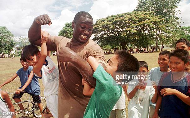 Sgt 1st Class Douglas Womack of Warner Robbins Georgia shows off his muscles to a group of kids March 23 2002 at Edwins Air Force Base in the...