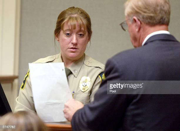 Sgt. Amanda Lambert of the Prince William County, Virginia detention center, looks at a sheet of evidence presented to her by Prince William county...