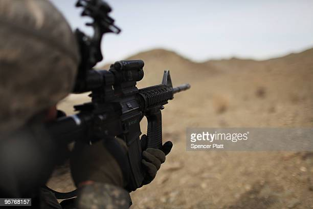 Sgt Anthony McGee from Arizona and part of a Provincial Reconstruction Team looks through a rifle scope during a patrol in an area prone to ambushes...