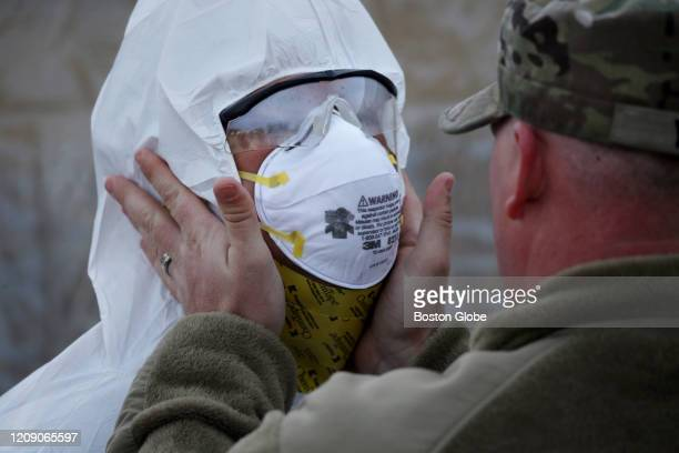 Sgt Brandon Young right helps Spc Brandon Bessette of the Rhode Island Army National Guard dress in personal protection equipment while preparing to...