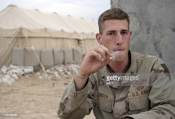 Sgt Dave Bowden with Alpha Company 1st Infantry Division smokes a cigarette in camp following the company's battle with insurgents for control of the...