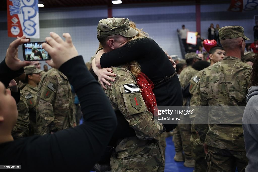 Sgt. D.J. Diener of the U.S. Army's 3rd Brigade Combat Team, 1st Infantry Division, embraces his wife Jackie Diener following a homecoming ceremony in the Natcher Physical Fitness Center on Fort Knox on Thursday, February 27, 2014 in Fort Knox, Ky. About 100 soldiers returned to Fort Knox after a nine-month combat deployment conducting village stability operations and working alongside Afghan military and police forces.
