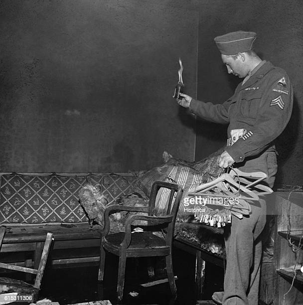 Sgt Ernest Pappas holds coat hangers and a loop of keys he found in Hitler's air raid shelter deep below ground next to the Chancellory Berlin...