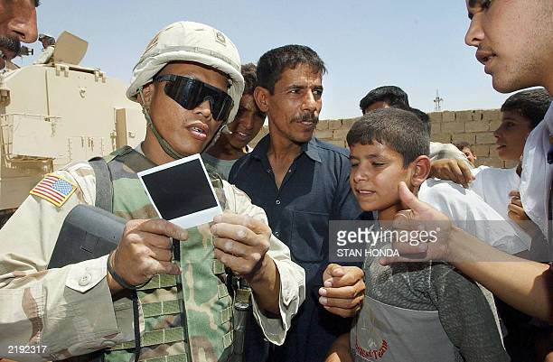 Sgt First Class John LaCuesta of Reno NV from the US Army 1st Brigade 9th Field Artillery shows a Polaroid photograph he took of a group of Iraqi...