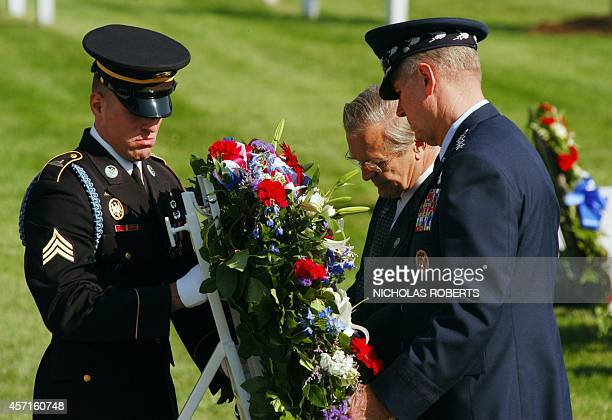 Sgt Gregory Ashton 3rd US Infantry regiment helps US Secretary of Defense Donald Rumsfeld and Chairman of the Joint Chiefs of Staff General Richard...
