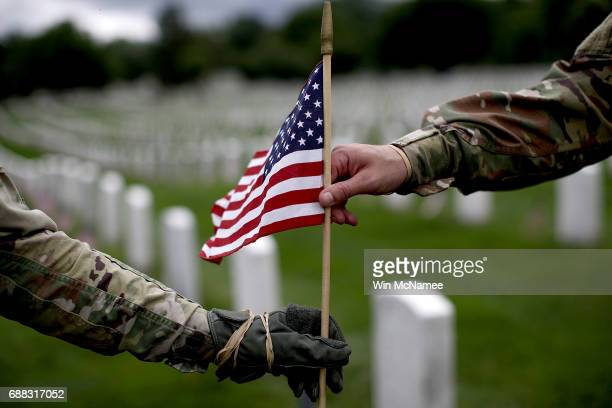 Sgt Iwona Kosmaczewska and Pvt 2 Wesley Defee members of the 3rd US Infantry Regiment place flags at the headstones of US military personnel buried...