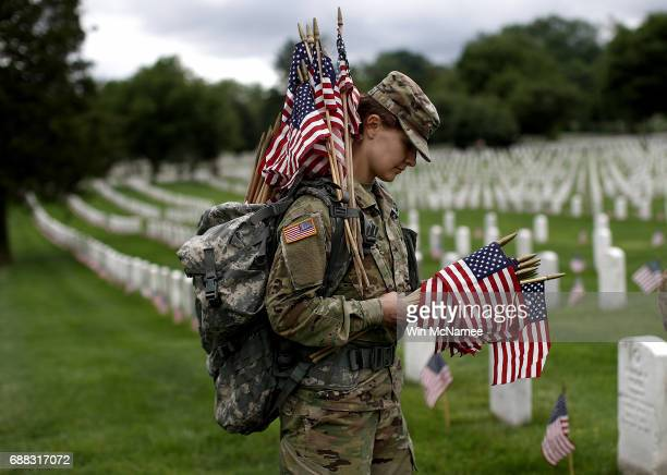 Sgt Iwona Kosmaczewska assists with the process of placing flags at the headstones of US military personnel buried at Arlington National Cemetery in...