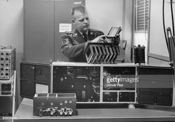 M Sgt Jack Bettis noncommissioned officer in charge of Precision Photo Engineering Branch of school at Lowry Air Force Base shows machine that does...