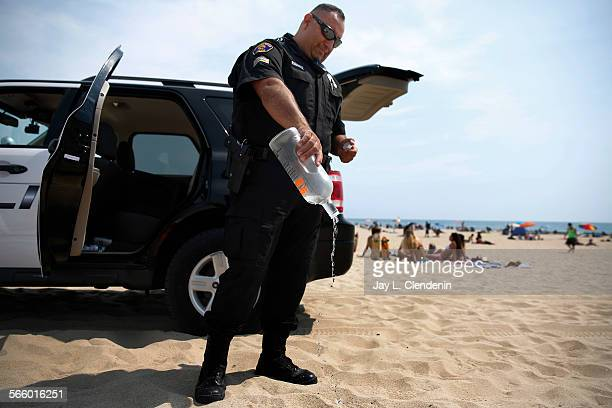 Sgt Jaime Ramirez with the Hermosa Beach Police Department empties a bottle of vodka he confiscated after issuing tickets to a couple of beach goers...