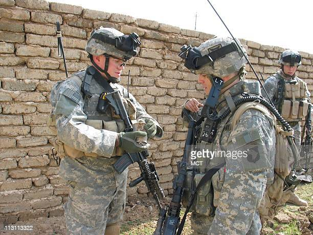 Sgt Josh Becherer of Ofallon Illinois left shows 1st Lt Dennis Call of Albuquerque New Mexico a piece of mortar equipment that insurgents had used to...