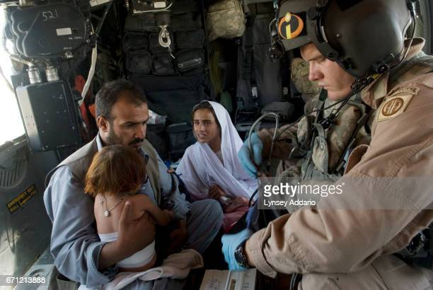 CORSAIR Sgt Joshua Sands medic tends to an Afghan girl Sophia who was burned in an accident in her home as her sister miriam holds her and her father...