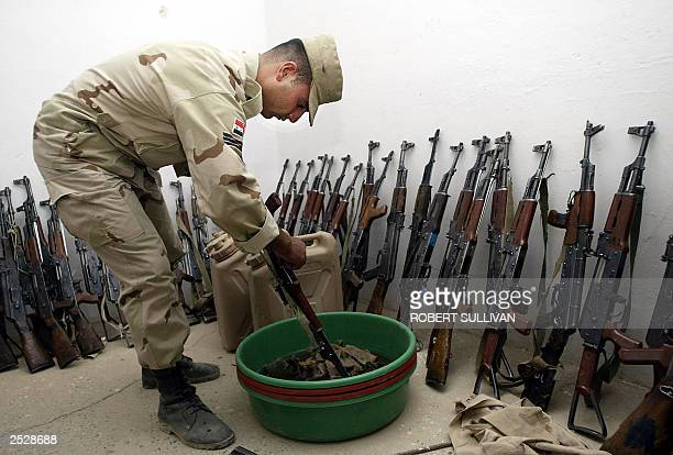 Sgt Kahtan Adnan Rifaat of the Alpha Company of the Iraqi Civil Defense Corp cleans AK47 rifles 23 September 2003 at Gizlany camp in Mosul northern...