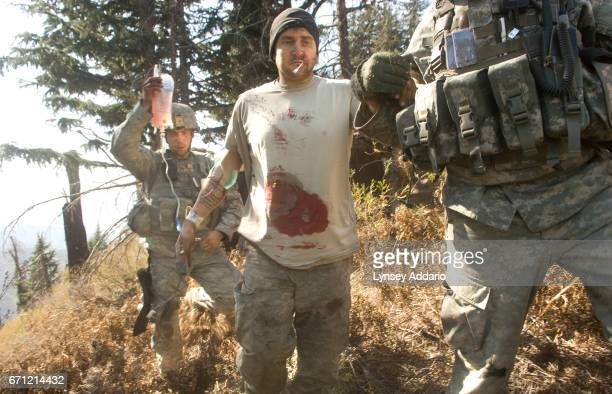 Sgt Kevin Rice is assisted as he walks to a medevac helicopter minutes after he was shot in the stomach during a Taliban ambush which killed one...