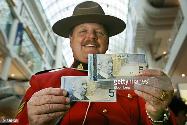 Sgt Moshe Gordon head of the force's anti counterfeiting force in Ontario holds up the new $5 dollar Canadian bill right along with the old bill in...