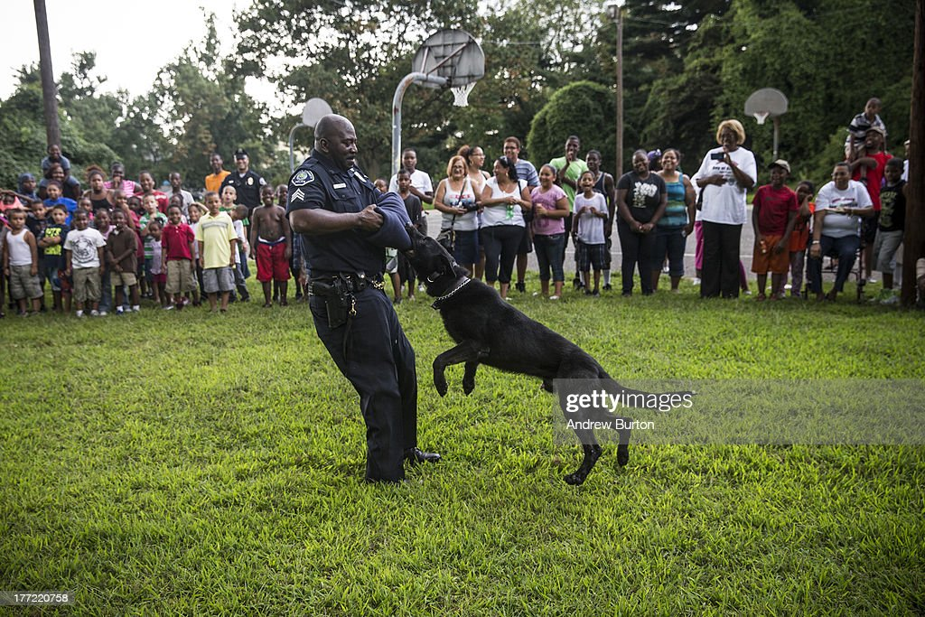 Sgt. Zsakhiem James, of the Camden County Police Department (CCPD), performs with his K9 partner, named 'Zero,' during a day of action, organized by the CCPD, which included cleaning up Farnham Park, on August 22, 2013 in the Parkside neighborhood of Camden, New Jersey. The town of Camden, which was once a large industrial town but watched it's population dwindle as manufacturing left, has been marred with societal problems including high unemployment, crime, murder and heavy drug trafficking for decades. The Camden County Police Department was officially created in May, 2013, after the unionized Camden Police department was disbanded. The overhaul, which was supported by New Jersey Governor Chris Christie, has been considered unprecendented and has been closely watched around the country. The new force currently has approximately 280 members, and will reach full size by December, with 400 members. Early signs suggest the overhaul has been effective - The Wall Street Journal reported earlier this month that Camden murder rates fell 29% from May, 2013 to July 2013, compared to the same period last year. Absentee rates of the CCPD is also lower: approximately 5% of officers have been reported absent so far, compared to approxmiately 30% of the Camden Police Department prior to the change in command.