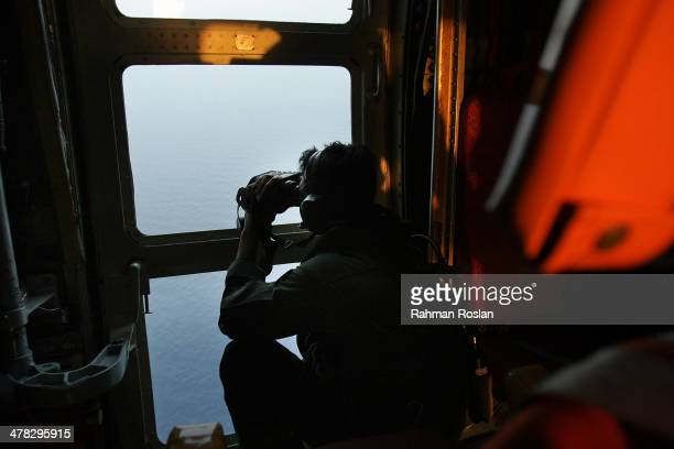 Sgt. Zulhelmi Hassan of the Malaysian Air Forces searches the water for signs of debris from the Malaysian airliner during a search and rescue...