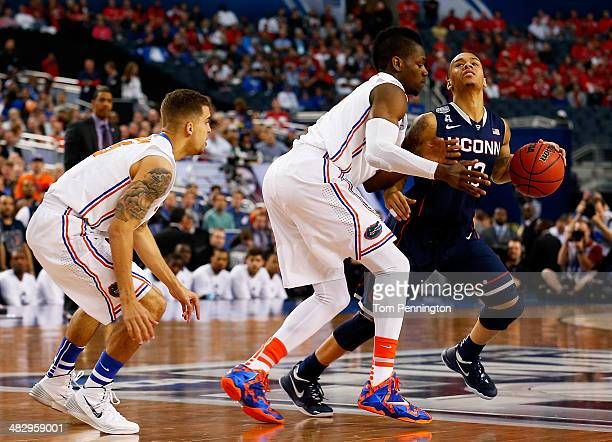 Shabazz Napier of the Connecticut Huskies controls the ball as Will Yeguete of the Florida Gators defends during the NCAA Men's Final Four Semifinal...