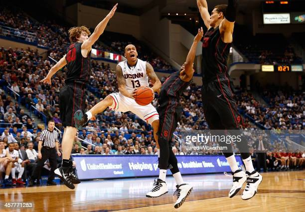 Shabazz Napier of the Connecticut Huskies goes up for a layup in the second half in front of John Gage and Anthony Brown of the Stanford Cardinal...