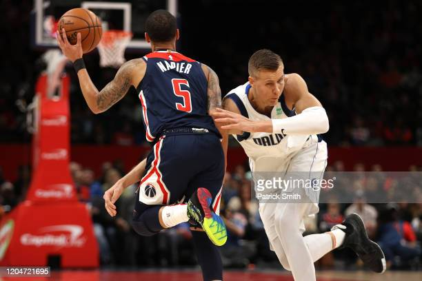 Shabazz Napier of the Washington Wizards is fouled by Kristaps Porzingis of the Dallas Mavericks during the first half at Capital One Arena on...