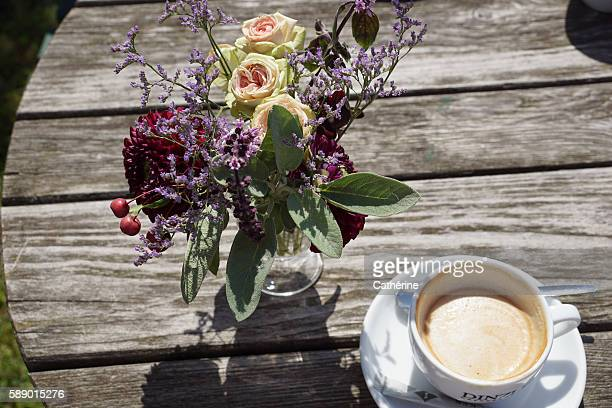 Shabby chic: flowers and coffee cup on wooden ground